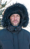 Portrait of confident man wearing fur hooded parka coat at the s — Stock Photo
