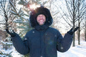 Smiling man wearing fur hooded parka coat in the winter park — Stock Photo