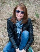 Young woman in a black jacket and jeans sitting on the hay — Stockfoto