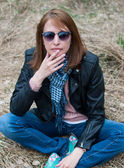 Young woman in a black jacket and jeans sitting on the hay — Stok fotoğraf