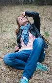 Young woman in a black jacket and jeans sitting on the hay — Foto de Stock
