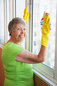 Smiling elderly woman cleaning a window — Stock Photo