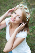 Girl in a wreath of flowers on a background of forest green — Stock Photo