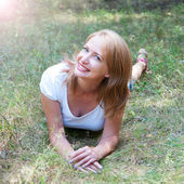 Beautiful girl lying in the grass whith lens flare effect — Stock Photo