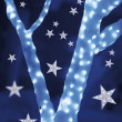 Stars on background of defocused blue lights and tree — Zdjęcie stockowe