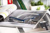 Reading glasses endorsed on a magazine at home — Stock Photo