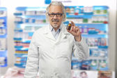 Caucasian mature male pharmacist on bright background of a pharm — Stock fotografie