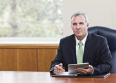 Mature Businessman using tablet computer — Stock Photo