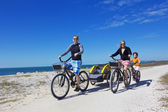 Family on a beach bicycle ride together — Stock Photo