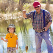 Little Boy and His Grandpa catching a fish — Stock Photo #40407213