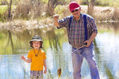 Little Boy and His Grandpa catching a fish — Stock Photo