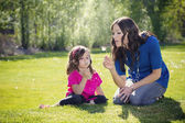 Mother Blowing Dandelions with daughter — Stock Photo