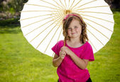 Cute little girl holding a parasol outdoors — Stock Photo