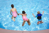Three Kids jumping into the Swimming Pool — Stock Photo