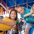 Kids having fun on a carnival carousel — Stock Photo