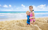 Crianças construindo castelos de areia na praia — Fotografia Stock
