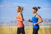 Female Runners on a jog outdoors (side view) — Stock Photo