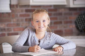Cute little girl writing and studying in her notebook — Stock Photo