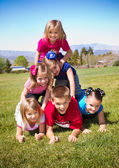 Cute Kids Building a Human Pyramid outdoors — Stock Photo
