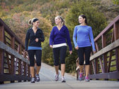 Three attractive young women talking a walking together — Stock Photo