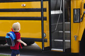 Child getting on a school bus — Stock Photo