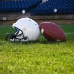 Football helmet on a stadium field — Stock Photo #40859137