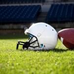 Football helmet on a stadium field — Stock Photo #40859163