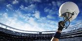 Football player raises his helmet — Stock Photo