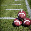 Stock Photo: Footballs on football field