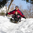 Stock Photo: Family having fun together snow sledding