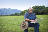 Old Farmer Adapting to the computer age — Stock Photo