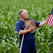 Old farmer holding the U.S. flag — Stock Photo #41242585