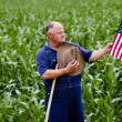 Old farmer holding the U.S. flag — Stock Photo