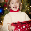 Little girl opening gifts on Christmas morning — Stock Photo