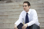 Jobless Young Businessman sitting on the stairs — Stock Photo