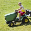 Middle-Aged Man Mowing lawn on riding mower — Stock Photo