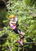 Young girl on a jungle zipline — Stock Photo