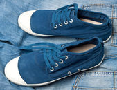 A pair of new blue shoes on a jeans — Stock Photo