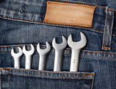 Wrenches in blue jeans pocket — Stock Photo