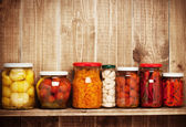 Preserved autumn vegetables on shelf near a wooden wall — Stock Photo