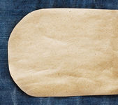 Paper tag on blue denim jeans — Stock Photo