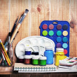 Paintbrushes, watercolor, gouache and paper are on wooden shelf — Stockfoto #25942497
