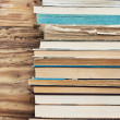 Stock Photo: Books next to wooden wall