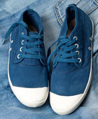 Ett par nya blå skor på en jeans — Stockfoto