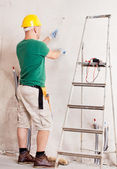 Electrician with knife cutting a wire — Stock Photo