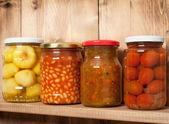 Konserwowanych warzyw na półce w pobliżu brązowe ściany drewniane — Zdjęcie stockowe