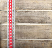 Red ribbon of hearts on old wooden background — Stock Photo