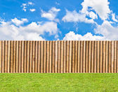 Half round post and rail fence with skies and green lawn horizontal seamless — Stok fotoğraf