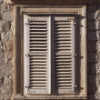 Mediterranean stone window with wood shutters — Stock Photo