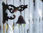 Vintage cast-iron bell on white painted fence — Stock Photo